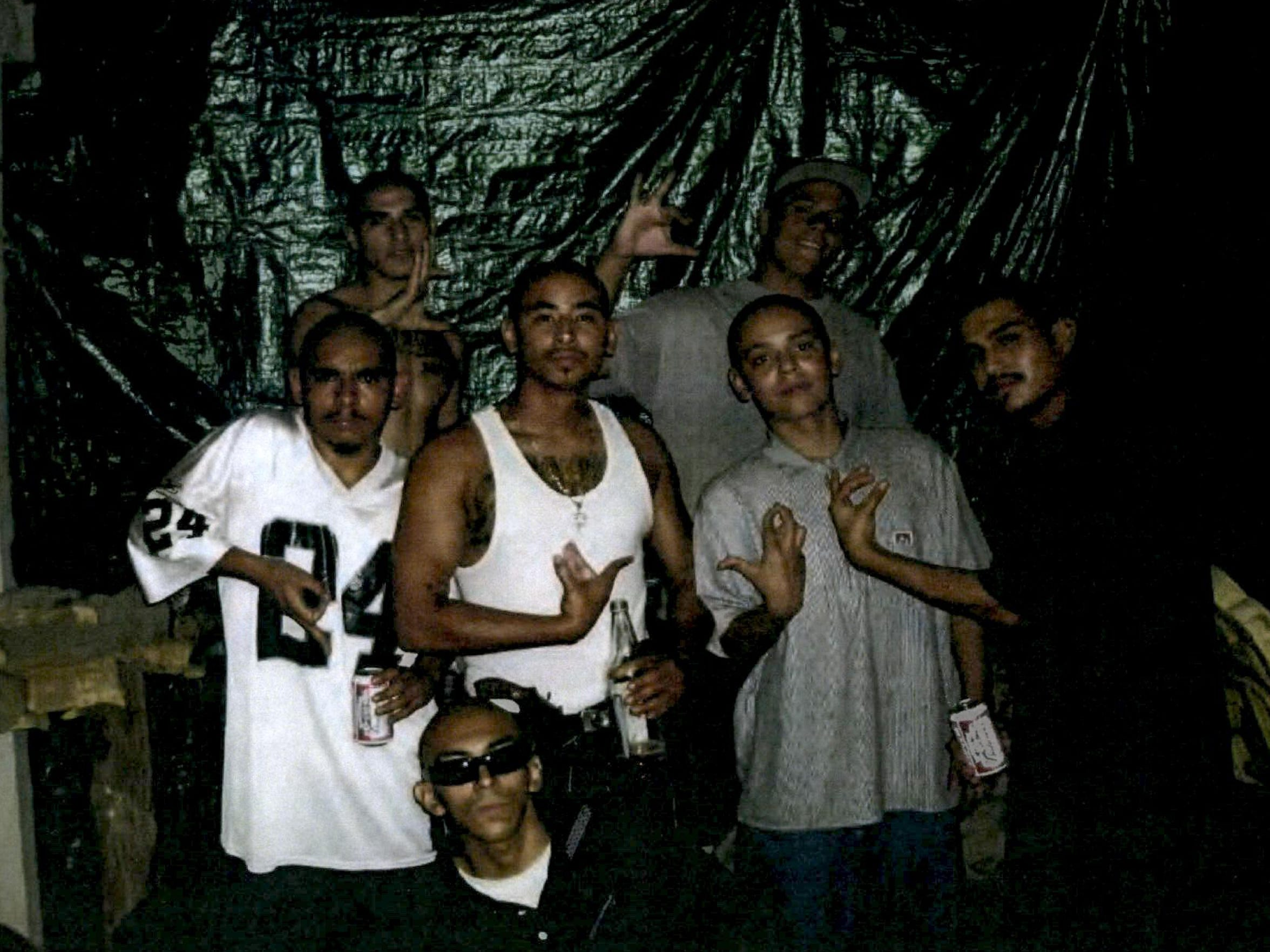 A group of unidentified men flash gang signs in a photograph
