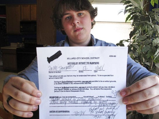 Jacob Shoemaker, 18, holds a copy of his school suspension