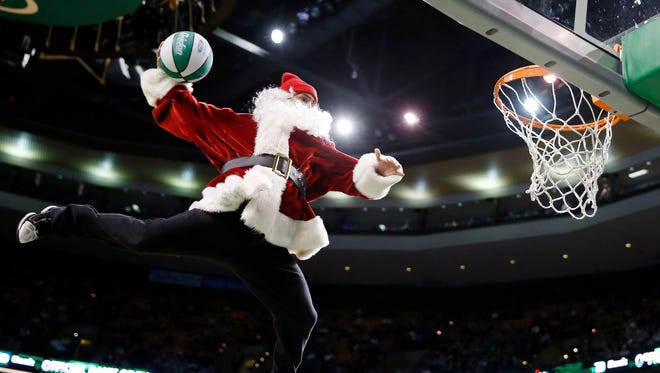 A performer in a Santa Claus costume makes a trick dunk during a timeout in the fourth quarter of an NBA basketball game between the Boston Celtics and the Minnesota Timberwolves in Boston, Monday, Dec. 16, 2013.