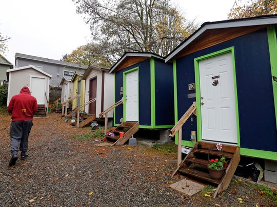 Tiny houses at a homeless encampment in Seattle where full size homes stand behind. Seattle Mayor Jenny Durkan wants to move hundreds more homeless people into tiny homes, emergency shelters and other immediate housing in the next 90 days.