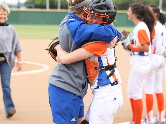 San Angelo Central High School assistant coach Kayla Matthews hugs senior catcher Mick Jones, who caught the ceremonial first pitch before the District 8-6A finale against Killeen Shoemaker at the Central Softball Complex on Friday, April 20, 2018. Jones has been sidelined all season with a medical condition.