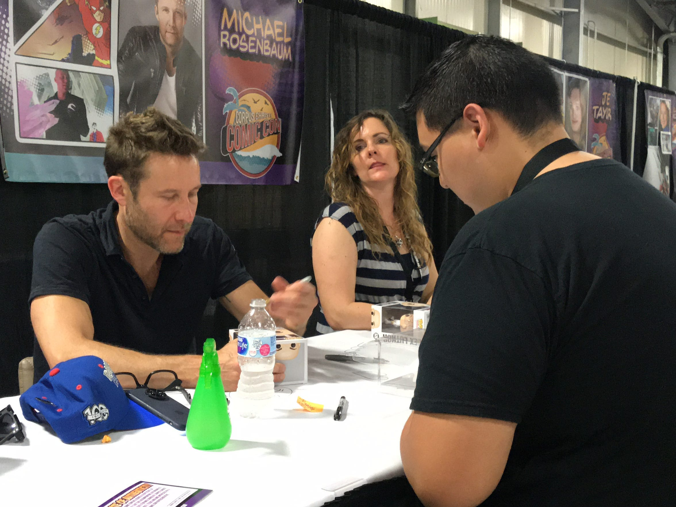 Actor Michael Rosenbaum signs a fan's pop figure at