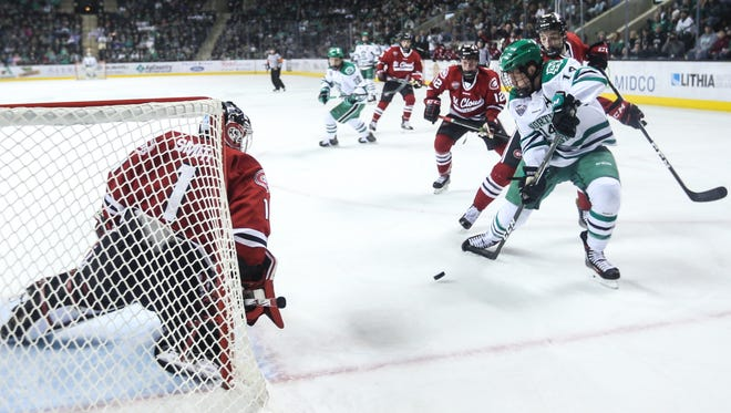 North Dakota's Austin Poganski (right) takes a shot against St. Cloud State's Jeff Smith during a Feb. 3 game at Ralph Engelstad Arena.