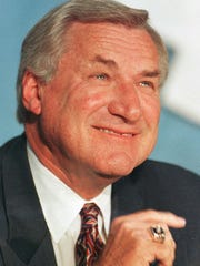 """AP Dean Smith in October 1997, when he announced his retirement after 879 victories. FILE - In an Oct. 9, 1997 file photo, North Carolina basketball coach Dean Smith smiles during a news conference in Chapel Hill, N.C.,where he announced his retirement. Smith, the North Carolina basketball coaching great who won two national championships, died """"peacefully"""" at his home Saturday night, Feb. 7, 2015, the school said in a statement Sunday from Smith's family. He was 83. (AP Photo/Bob Jordan, File)"""