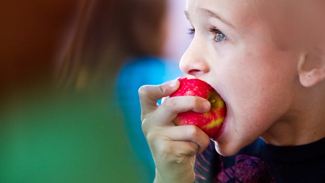 Encourage schools to take advantage of farm to school programs that incorporate locally grown produce in the school lunch menu. | FILE PHOTO: Second-grader Bryson Freehan, 7, munches on a fresh, locally grown organic apple during lunch at Meyer Elementary School in Tempe.