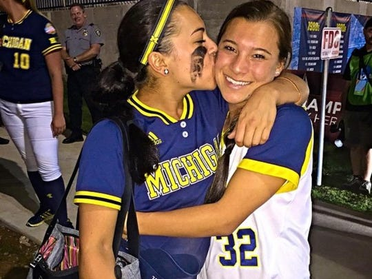 Michigan softball star Sierra Romero smooches sister Sydney, who plays for Oklahoma. They face each other Friday in their home state of California.