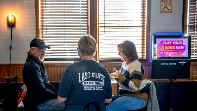 Aaron Reed and his wife, Audrey, of Farmington share a laugh with waitress Debra Bednar during lunch Sunday at the Last Chance Bar & Grill in Alta. Bednar, 63, a longtime server at the popular pub, just worked her first weekend since the beginning of the pandemic.