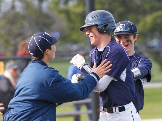 Brighton's Ernie Clement, center, gets congratulations after an in-the-park home run.