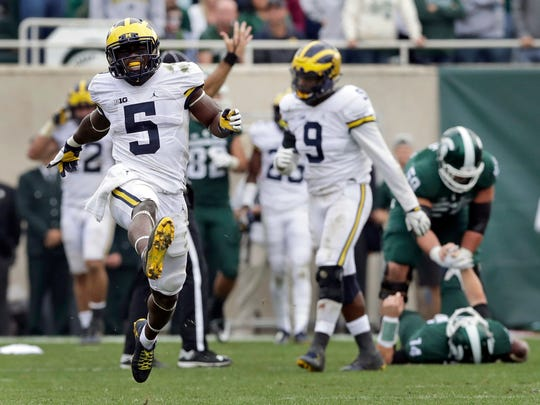 FILE - In this Oct. 29, 2016, file photo, Michigan linebacker Jabrill Peppers (5) celebrates after sacking Michigan State quarterback Brian Lewerke (14) during the second half of a college football game, in East Lansing, Mich. Peppers was voted the defensive player of the year for The Associated Press All-Big Ten football team, selected Monday, Dec. 5, 2016. (AP Photo/Carlos Osorio, File)