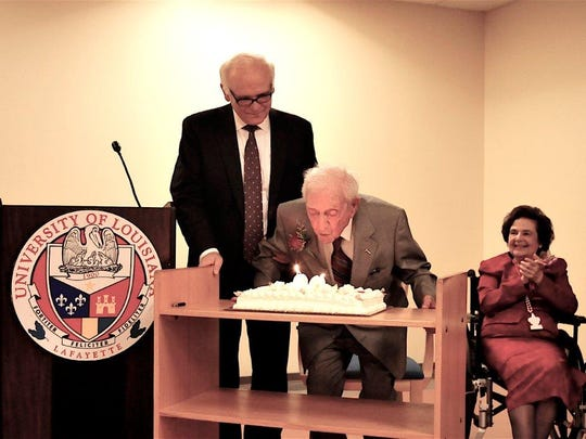 Kaliste Saloom,Jr. blows out birthday candles during a celebration of his 99th birthday.