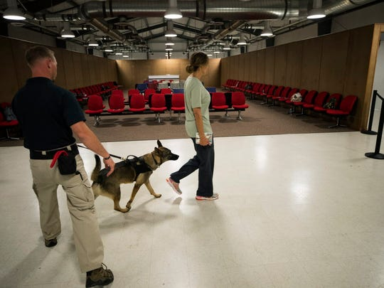 Transportation Security Administration canine training instructor John Peeler with Biko, a German shepherd, screens role-playing passengers in a replica of an airport terminal at TSA's National Canine Training Center in San Antonio on Sept. 13, 2017, to teach the dog how to search for explosives in an airport.