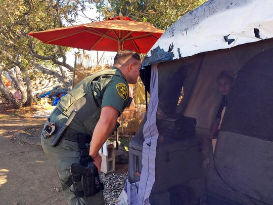 An Orange County sheriff's deputy calls to residents inside a tent in Anaheim, Calif., Monday, Jan. 22, 2018, to let them know they'll need to leave the area and that the county will assist with the move if they need. Southern California authorities on Monday went tent to tent telling the homeless they're shutting down the large riverbed encampment some have called home for years.