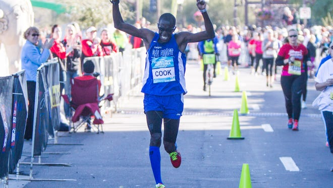 Roosevelt Cook throws his hands in the air before crossing the finish line as he wins the P.F. Chang's Rock 'n' Roll Arizona Marathon on Jan. 18th, 2015, in Tempe.