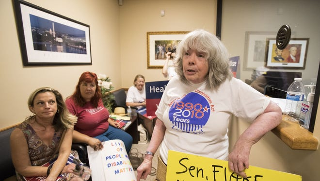 Amina Kruck (right) protests in the lobby of Senator Jeff Flake's office in Phoenix, Ariz. on Wednesday, July 5, 2017.