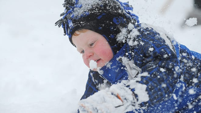 Bridger Wagner, 3, of Sioux Falls, plays in the snow outside his house during the first snow of the season Friday.