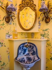 A downstairs bathroom in the Aqualane Shores home features an original chinoiserie blue and white antique sink.