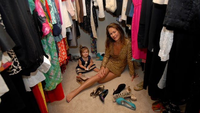 """With her young daughter Vizcaya at her side, Melissa Cunningham wears her shimmering gold Hugo Buscati dress while being surrounded by vintage clothing in her closet at her home in Naples. """"Every morning she pulls out my shoes (and more) while I'm getting dressed,"""" Melissa says."""