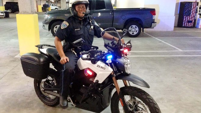 A San Mateo officers shows off the new electric motorcycle