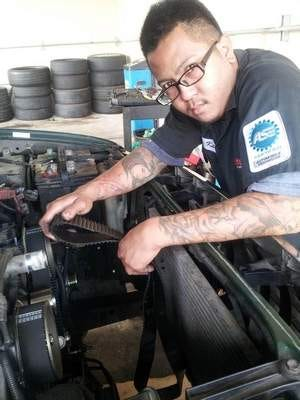 Screaming belts: Karl Dela Cruz, a certified mechanic and supervisor at United Tire in Tamuning, holds an old belt that was replaced in this truck.