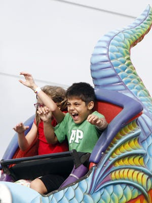 Hanna and Austin Lavi, visiting from Oklahoma, ride in the back of the Cobra Rollercoaster at Zoomers Amusement Park in Fort Myers.