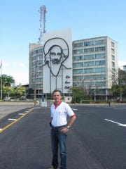 """Fernando """"Fritz"""" Riveron stands in front of one of the many murals throughout Cuba associated with the Cuban Revolution during his 2007 visit to his native country of Cuba."""