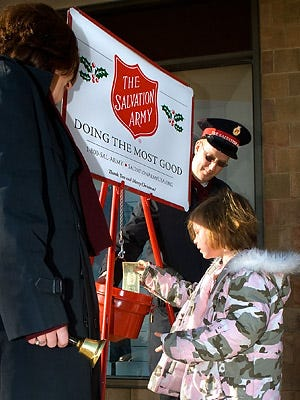 A child gives to the Red Kettle at a Publix.