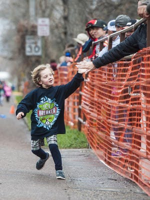 Ivan Damyanovich, 5, high-fives onlookers as he crosses the one mile race finish line during the 38th annual Ice Breaker Sunday.