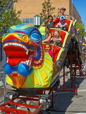 The Birmingham Village Fair runs through Sunday and is located near Shain Park in downtown. These children and experienced the thrills of the Chinese Dragon ride in this 2014 file photo.