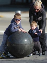 Courtney Clark and her two sons, Graham and Landon, enjoy the spring-like weather while fooling around at Shain Park.