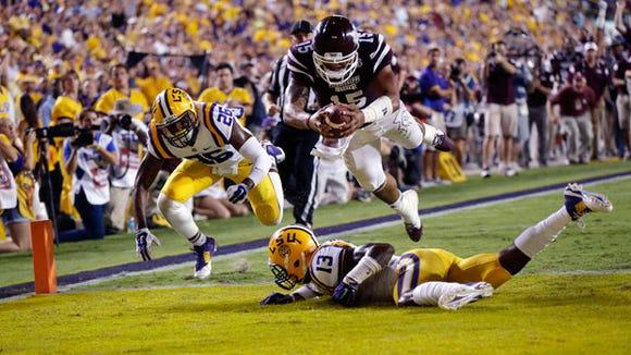 Mississippi State quarterback Dak Prescott leaps into