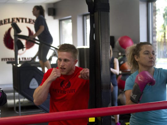 Matthew Strout (left) runs an exercise class with boxing with student Yelena Shayer of Manalapan at Relentless Fitness and Training, Freehold Township.