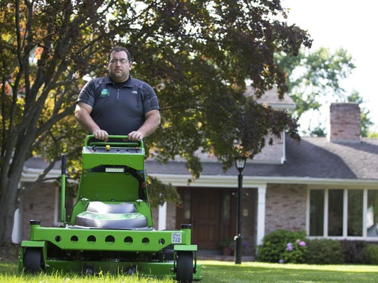 Steve Popp with Carbon Cutters uses an electric mower to cut grass at a home in Brighton on Friday, July 10, 2015.
