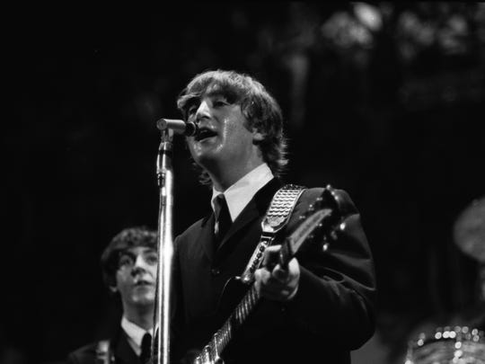 The Beatles' John Lennon sings while Paul McCartney looks on during the concert at Cincinnati Gardens in 1964.