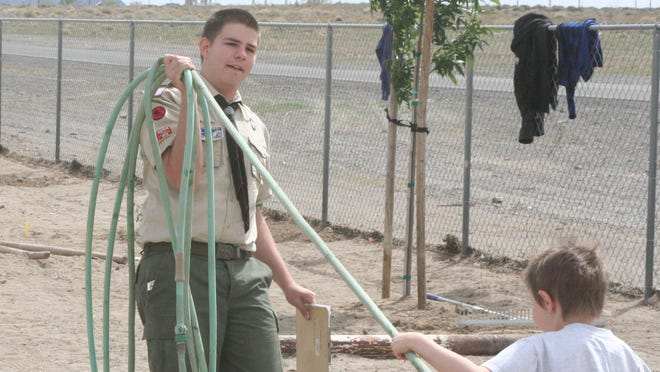 Josiah Thompson helps one of the volunteers water trees they planted at the Fernley Cemetery as part of his Eagle Scout project.
