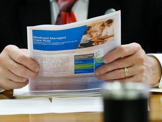 A member of the Senate Medicaid Committee reviews a Medicaid handout in 2018.
