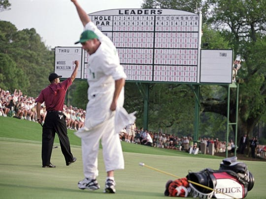 Tiger Woods and his caddie Steve Williams celebrate on the green after he wins the 2001 Masters at the Augusta National Golf Club in Augusta, Georgia. (Stephen Munday, ALLSPORT)
