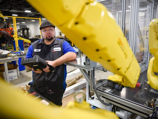 An automation technician at Central McGowan works on a new robotic unit Tuesday, Sept. 20, in St. Cloud.