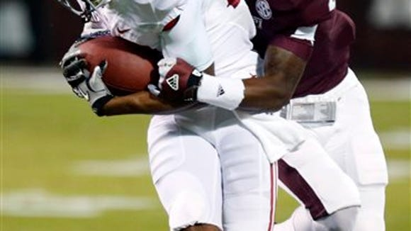Alabama wide receiver Christion Jones (22) is tackled by Mississippi State defensive back Will Redmond (2) after a short pass reception during the first quarter  of an NCAA college football game, Saturday, Nov. 16, 2013, in Starkville, Miss. (AP Photo/Rogelio Solis)