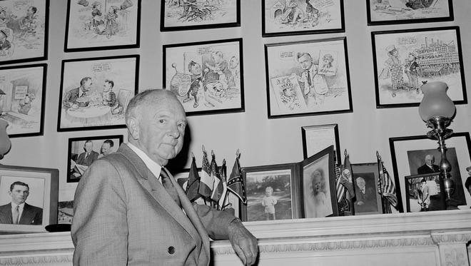 Sen. Harry F. Byrd (D-Va.)  leaning on the mantel in his office at the Senate Office Building in Washington, April 19, 1961.    Above the mantel are a wallful of cartoons which lampoon or praise him.   The cartoons also tell the story of a number of his battles since he entered the Senate in 1933.