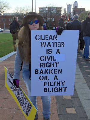 Daenna Newkirk of Des Moines, an opponent of the proposed Bakken pipeline, holds a sign outside the Iowa Capitol last year.