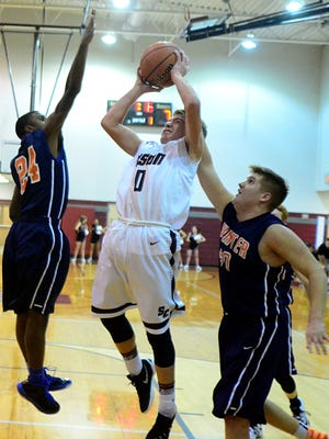 Station Camp Middle's Kyle Winter is fouled by Hunter's Will Crabtree (at right) as Chris Townsend (24) attempts to block Winter's shot during first-quarter action.