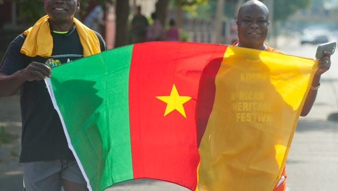 Isaac Nguepnan, of Spingfield, Ill., an immigrant from Cameroon gets some help carrying his former nation's flag from Francis Miller, right, formerly of Liberia and now living in Louisville. Both belong to soccer clubs that were to compete in the African Heritage Festival.