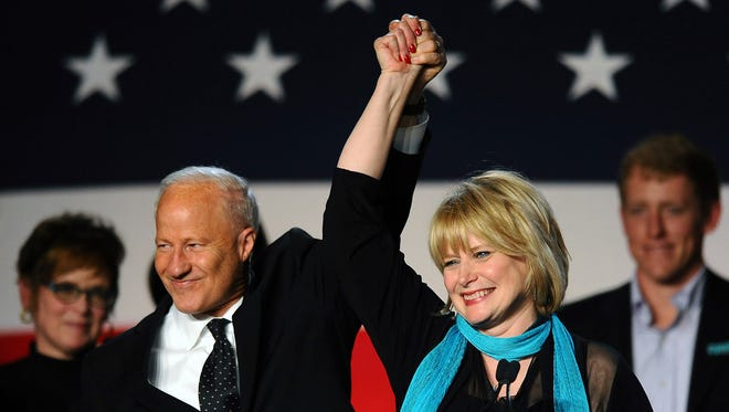 FILE- In this Nov. 4, 2014, file photo, U.S. Rep. Mike Coffman, R-Colo., left, celebrates with his wife, Colorado attorney general Cynthia Coffman, at an election night gathering at the Hyatt Regency Denver Tech Center in Denver. The Coffmans filed for divorce on Monday, June 19, 2017. (AP Photo/Chris Schneider, file)
