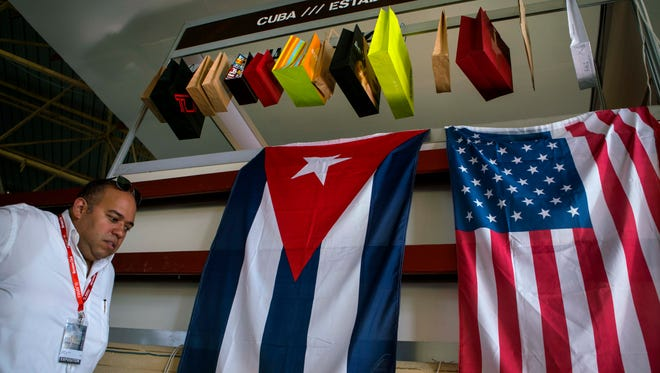 A man walks past Cuban and U.S. flags at the 33rd Havana International Trade Fair in Havana on Nov. 2, 2015.