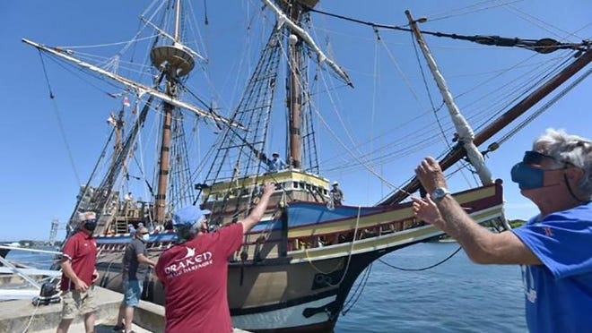 Crew member Dick Turner, right, reaches for a heaving line to help tie up the Mayflower II at Massachusetts Maritime Academy on Saturday. The replica of the ship that brought the Pilgrims to America will remain docked through the weekend and then begin its voyage under tow back to Plymouth Harbor on Monday morning.