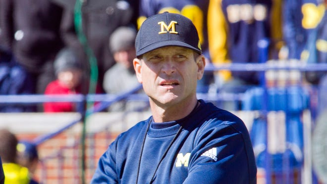 Michigan football coach Jim Harbaugh watchs players warm up in Ann Arbor on April 4, 2015.