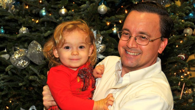 Isabella and Daddy Duty columnist Tim Walters have their picture taken in front of the Christmas tree at FLORIDA TODAY.