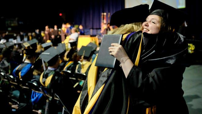 Emily Wilton, of Port Huron, gets a hug from professor Becky Lubbers during SC4's 2015 commencement ceremony at McMorran Arena.