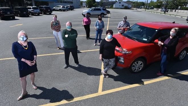 Elizabeth Wurfbain, left, executive director of the Hyannis Main Street Business Improvement District, joins Suzanne Fantaroni, Bill Ferrall, Susan Fernald, Amanda Converse, Ellen Brady, Gerald Garnick and Betsy Young in a parking lot off Main Street that they plan use for drive-in movies this summer to provide entertainment during the coronavirus pandemic.
