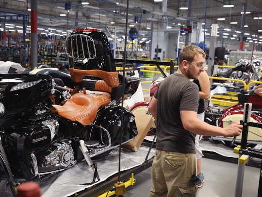 Workers put finishing touches on an Indian Roadmaster motorcycle at the end of the assembly line at the Polaris Industries factory on August 8, 2014 in Spirit Lake.